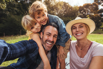 Cheerful family making selfie on picnic