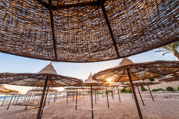 straw umbrellas on sandy sea (ocean) beach on exotic resort. summer landscape