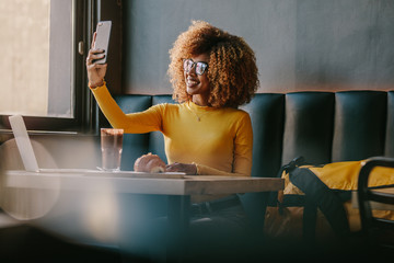 Smiling female traveller sitting at a coffee shop taking selfie