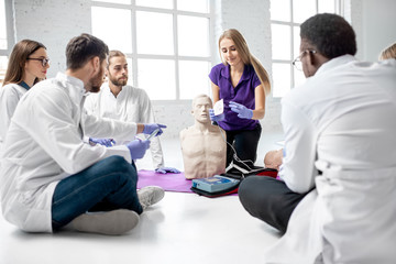 Group of young medics with instructor shows how to do defibrillation on the dummy during the first aid training indoors