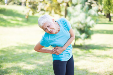 Senior fitness woman rubbing the muscles of her right side