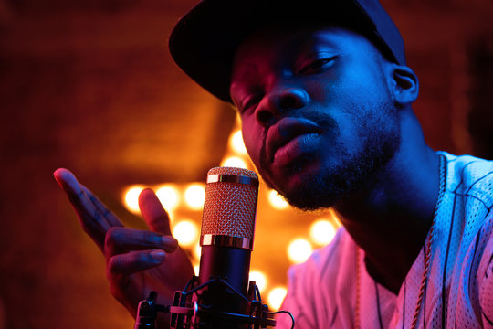 Young man with beard and mustaches in baseball cap and t-shirt sing in microphone and look in camera. Pink neon light