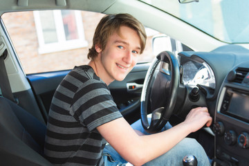 A Teenage boy and new driver behind wheel of his car Fototapete