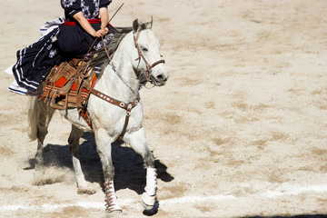 A mexican woman dressed as escaramuza rides her white horse