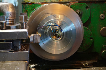 Machining of a round part on a lathe, facing by a worker on a mechanical feed. Chips fly in different directions.