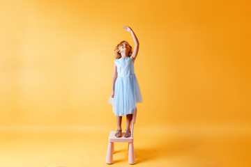 A little child girl in a blue dress is standing on a chair and measures her height against the background of the yellow wall. Concept of development, goal, success