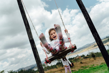 Smiling caucasian girl wearing colorful pants on a swing in a garden in Represa del Sisga, Colombia