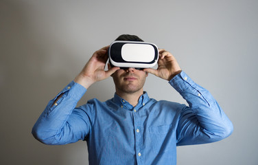 Handsome man in virtual reality goggles. Space for your text.