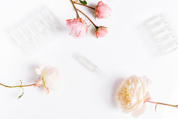 Elite facial skin care product in ampoule and roses on white background.