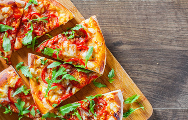 slices vegetarian Pizza with Mozzarella cheese, Tomatoes, pepper, Spices and Fresh arugula. Italian pizza. Pizza Margherita or Margarita on wooden table background