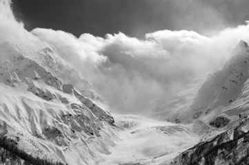 Fototapete - Glacier in fog, snowy mountain peaks and sunlight cloudy sky
