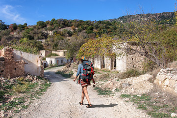 A girl with large backpack walks through the ruins of an abandoned Turkish village in Cyprus