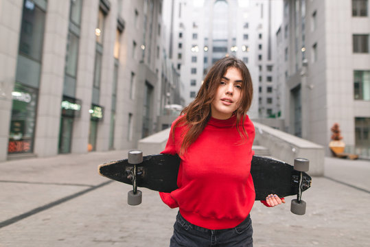 Stylish street girl in casual clothing is standing with a longboard in the hands of the background of modern architecture. Girl skater poses to the camera on the background of a modern building.