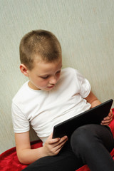 kid hold a digital tablet and looking