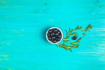 Set of black olives on plate and rosemary