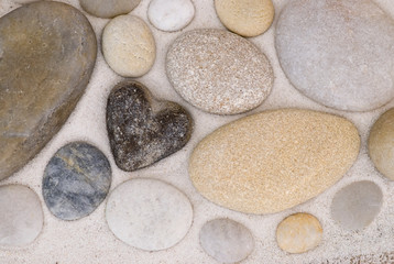 Smooth heart shaped pebbel with other ordinary pebble in sand