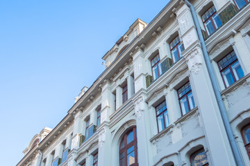 Beautiful facade of an old building with lots of windows, against a blue sky