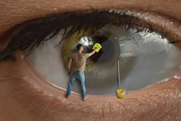 Male worker cleaning the surface of the pupil of the eye with a rag. Concept of healthy eyesight, conjunctivitis and window cleaning.