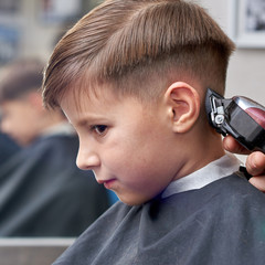 Hairdresser making a haircut to a boy with clipper.