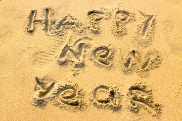Hand inscription Happy New Year on the sand.