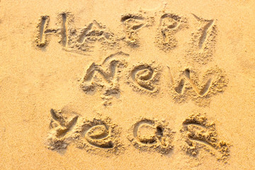 Handwriting Happy New Year on the sand.