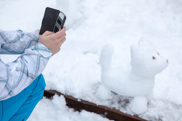 Human hands photographs snowman the dog on cell phone in park at winter