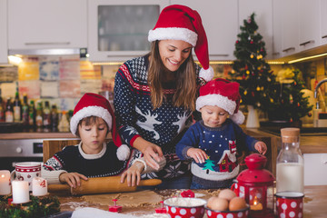 Sweet toddler child and his older brother, boys, helping mommy preparing Christmas cookies at home