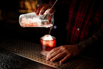 Bartender pouring a delicious Boulevardier cocktail from the measuring cup