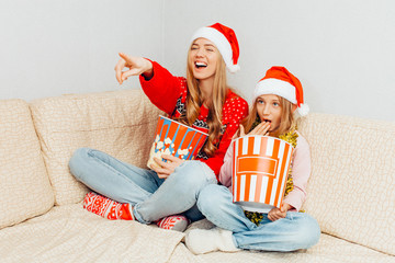 Mom and her little daughter, dressed in Santa Claus hats, watch movies and eat popcorn while sitting on the couch.