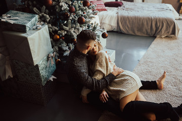 The attractive couple on Christmas at home near Christmas tree, embracing each other. New Year's photo young man and girl in the Christmas interior, cozy decorated house .
