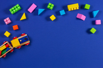 Wooden toy train with colorful cubes on blue background
