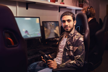 A young Indian guy wearing a military shirt sitting on a gamer chair and looking at a camera in a gaming club or internet cafe.