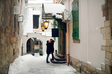 Happy young couple kissing on the stairs in the small alley between houses. Winter time.