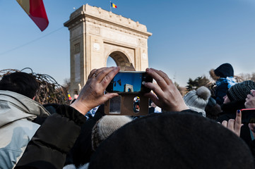 People taking pictures of the Triumphal Arch with their smartphones during the National Day parade in Bucharest, Romania