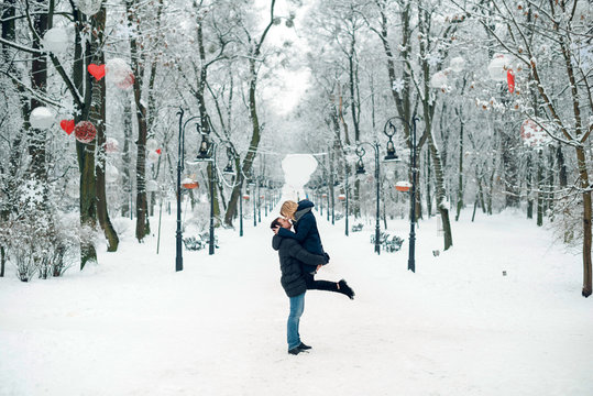 Happy young couple kissing and hugging while walking in the snowy park on beautiful winter day. Valentines Day.AC