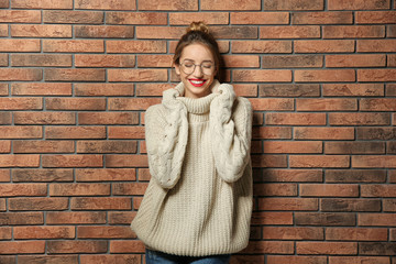 Wall Mural - Beautiful young woman in warm sweater near brick wall
