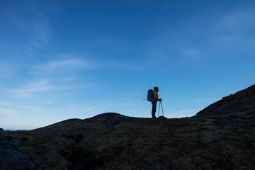 Hiker standing on mountain ridge, Moskenesoya, Lofoten Islands, Norway