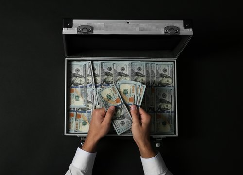 Businessman counting money over suitcase on dark background, top view