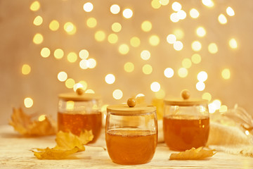 Glass jars with sweet honey on table against blurred lights. Space for text
