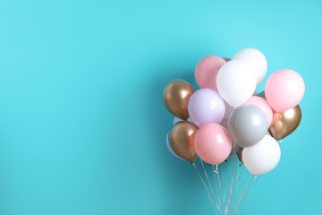 Colorful party balloons on blue background. Space for text