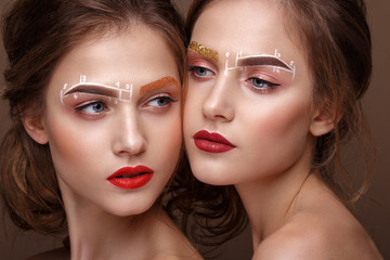 Two girls are twin sisters with an unusual eyebrow makeup. Beauty face.