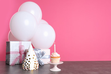Composition with birthday cupcake, presents and balloons on table. Space for text