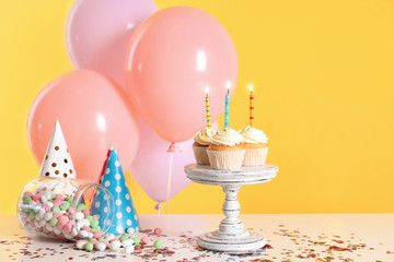 Composition with birthday cupcakes and balloons on table