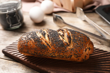 Board with freshly baked poppy seed roll on table