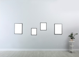 Frames with empty canvases on wall in modern art gallery. Mockup for design