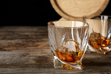 Golden whiskey in glass with ice cube on wooden table