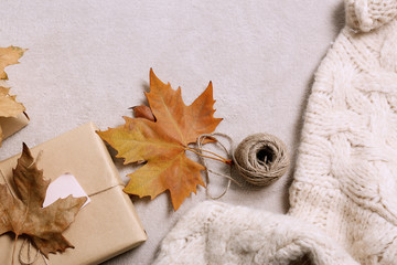 Flat lay composition with warm sweater on gray background