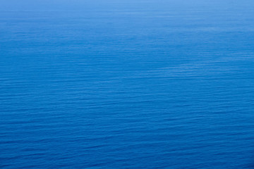 Aerial view of the clear blue sea surface on a bright sunny day.