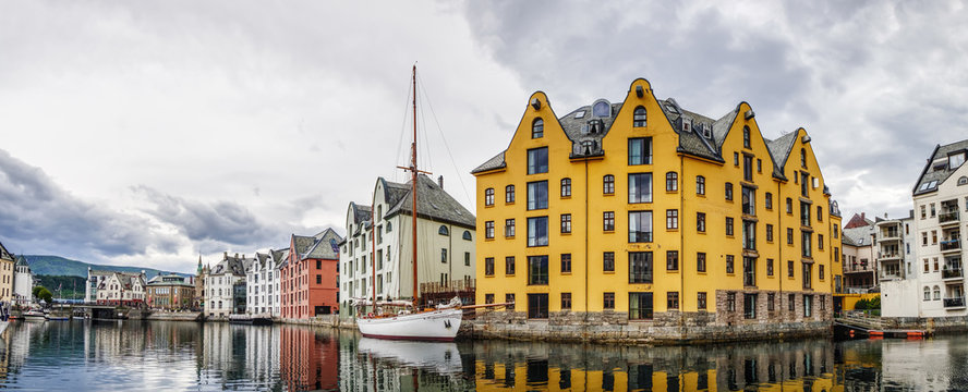 Yachts and boats at the waterfront of Alesund town, old architecture of Alesund city centre on the background, Norway