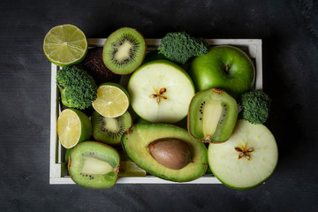 Green fresh fruits in a tray on the kitchen table. Above view
